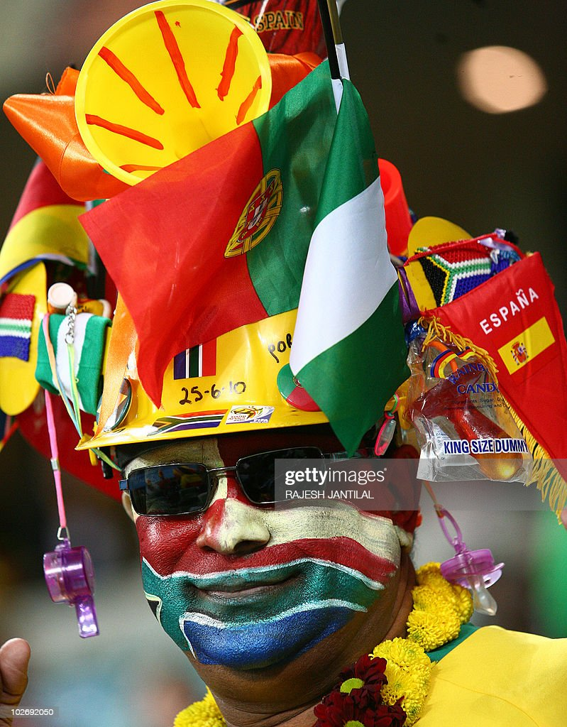 A supporter with the South African colours and wearing a makarapa decorated with various flags smiles in the stands during the 2010 FIFA World Cup...