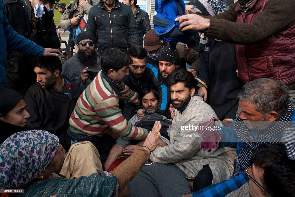 Supporters and activists of Jammu and Kashmir Liberation Front (JKLF) comfort the chairman of JKLF <a gi-track='captionPersonalityLinkClicked' href=/galleries/search?phrase=Yasin+Malik&family=editorial&specificpeople=691200 ng-click='$event.stopPropagation()'>Yasin Malik</a> after Indian government forces fired teargas shells towards him during a demonstration on December 24, 2014 in Srinagar, the summer capital of Indian administered Kashmir, India. Hundreds of supporters and activists of Jammu and Kashmir Liberation Front (JKLF) a pro independence resistance party, clashed with Indian government forces on Wednesday in Srinagar, as JKLF chairman <a gi-track='captionPersonalityLinkClicked' href=/galleries/search?phrase=Yasin+Malik&family=editorial&specificpeople=691200 ng-click='$event.stopPropagation()'>Yasin Malik</a> along with his supporters staged a sit-in to protest alleged atrocities, arrests and raids by Indian police. Malik was among hundreds of Kashmir resistance leaders and activists arrested by Indian police in the run up to the five-phased Assembly polls. He was released last night after a two-month-long detention, a JKLF spokesman said.