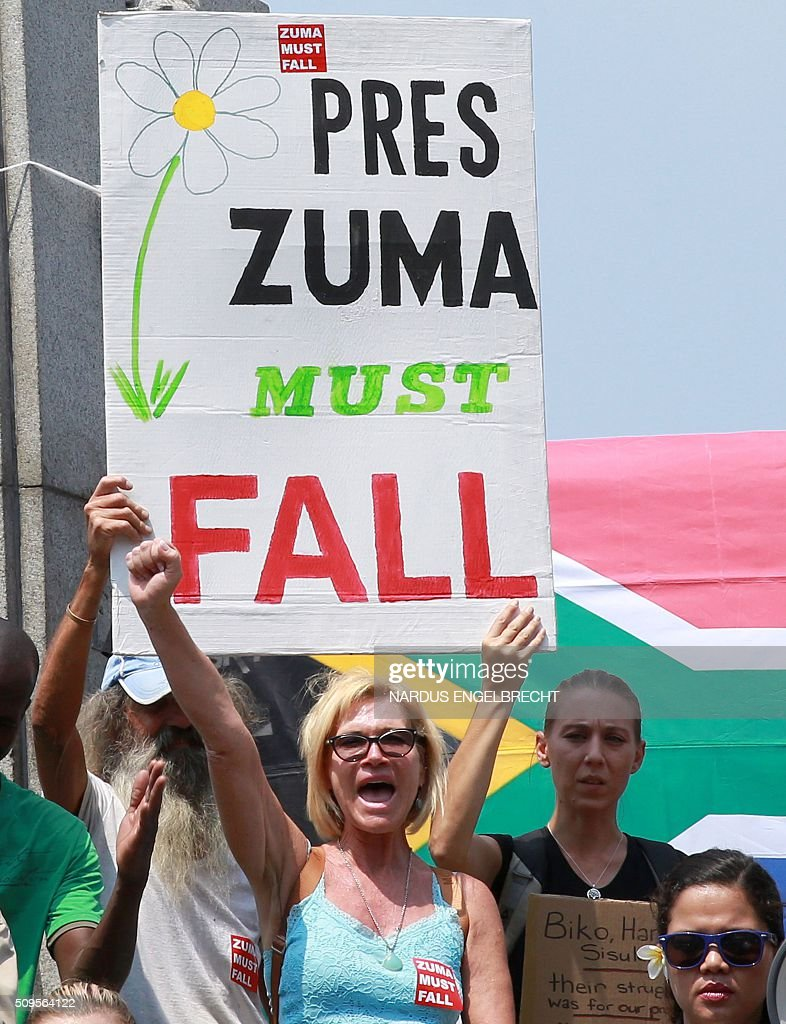 #ZUMAMUSTFALL supporters and campaigners demonstrate against South African President Jacob Zuma on February 11, 2016 in Cape Town, South Africa few hours ahead of his State of the Nation address. Police erected razor wire barricades outside the South African parliament on February 11 ahead of President Jacob Zuma's address to the nation against a background of concerted efforts to oust him from office. / AFP / NARDUS ENGELBRECHT