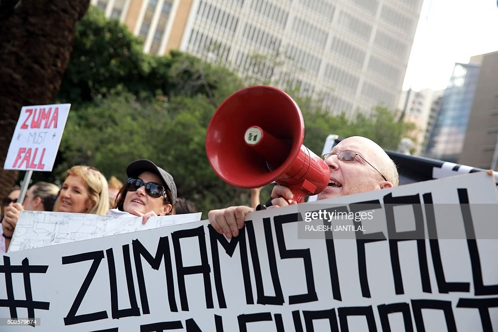 #ZUMAMUSTFALL supporters and campaigners hold banners reading slogans against South African president Jacob Zuma as they demonstrate and shout slogans on February 11, 2016 in Durban, few hours ahead of his annual State of the Nation Address (SONA)at the South African Parliament in Cape Town. Factors fuelling the calls for Zuma to quit include public money spent on his private residence, damage done to the economy when he fired two finance ministers within days, and government corruption. His address to parliament comes just two days after the Constitutional Court heard a crucial case accusing the president of violating his oath to uphold the constitution. JANTILAL