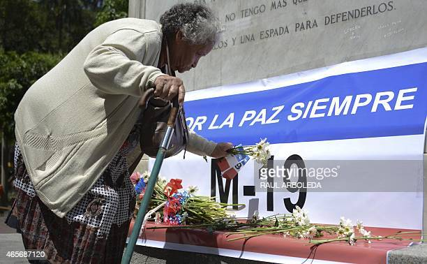 Supporters and former M19 guerrilla fighters put flowers on an M19 flag during the commemoration of the 25th anniversary of the peace agreements with...