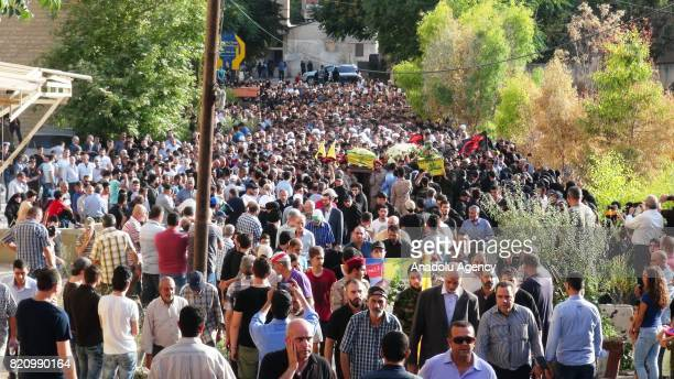 Supporters and members of Hezbollah attend the funeral of two of their comrades killed on day two of an Iran backed military operation against Syrian...