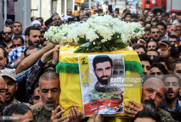Supporters and members of Lebanon's Shiite Muslim movement Hezbollah carry the coffin of a fallen comrade killed during a military operation against...