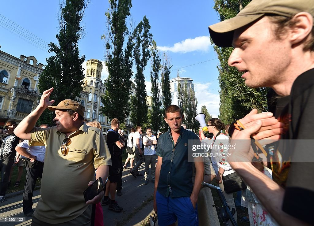 Supporters and opponents of Communists idea argue as hundreds of policemen guard a Soviet era monument for Bolshevik and Red Army commander Nikolai Shchors in the center of Kiev on June 30, 2016, to prevent it dismantling. Activists of some nationalists parties and the movements accused the Kiev city government of inaction in the implementation of the Decommunisation Law and were going to destroy the monument of the 'butcher of Ukrainian people'. The monument to Red Divisional Commander of the Bolshevik Revolution and the Civil War in 1917 was opened in 1954 to mark the 300th anniversary of the reunification of Russia and Ukraine. / AFP / SERGEI
