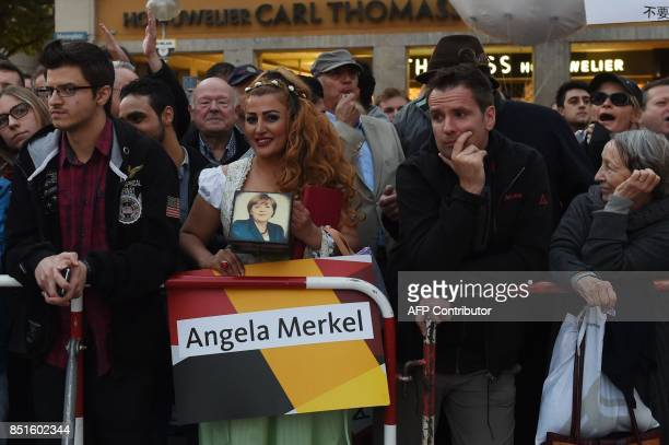 Supporters and opponents of German Chancellor Angela Merkel listen as she addresses an election campaign rally in Munich southern Germany on...