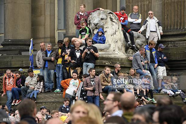 Supporters are pictured at the departure village in front of the city hall before the start of the 1905 km first stage of the 101st edition of the...