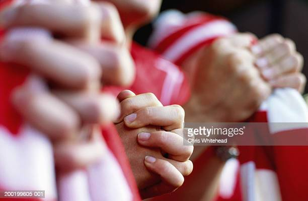 Supporters at football match, close-up of clutched hands