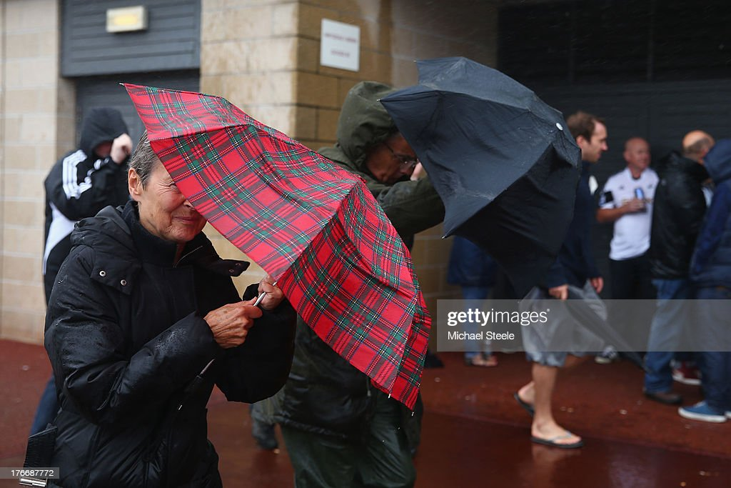 Supporters brave the torrential rain as they arrive ahead of the Barclays Premier League match between Swansea City and Manchester United at the Liberty Stadium on August 17, 2013 in Swansea, Wales.