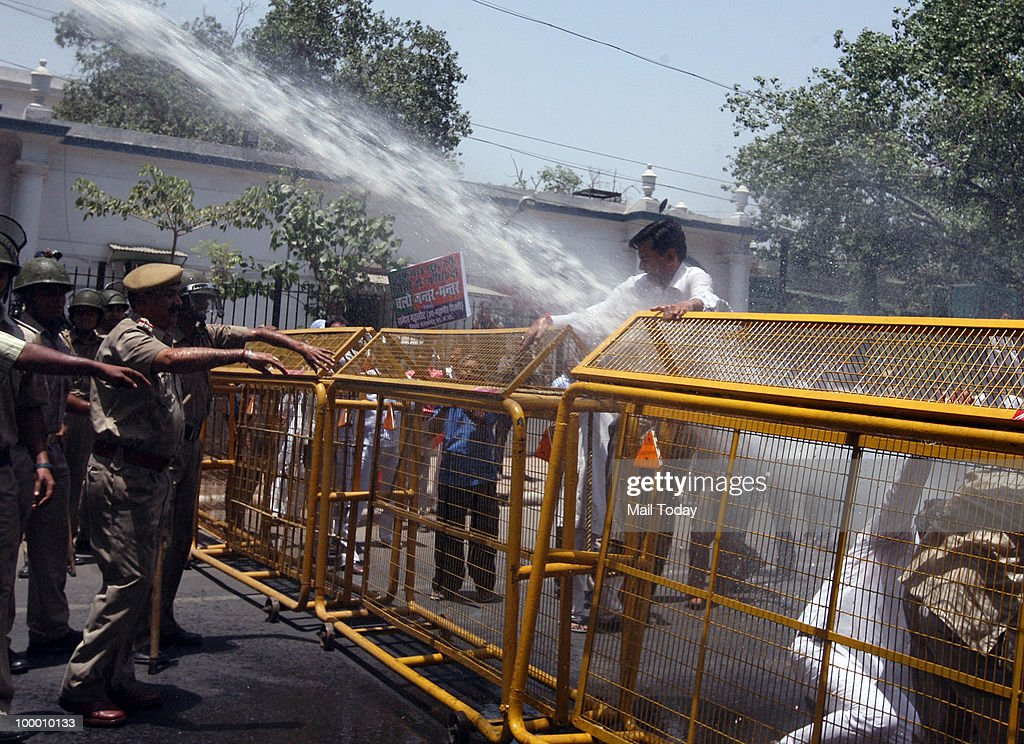 BJP supporters brave water canons, being used by the police, during a protest against the delay in hanging of Afzal Guru in New Delhi on May 19, 2010.