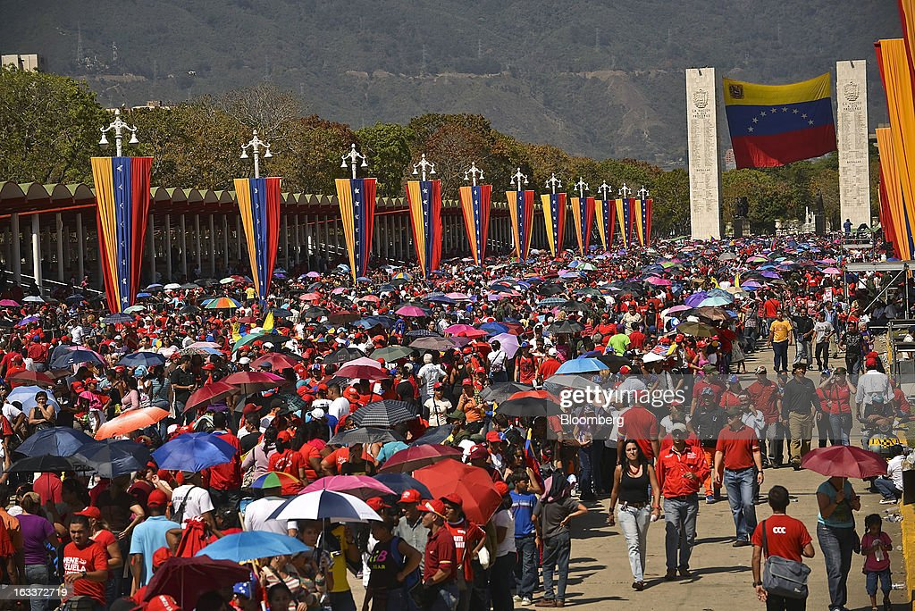 Supporters carry umbrellas while gathering to pay their respects during the funeral for Venezuelan President Hugo Chavez in Caracas, Venezuela, on Friday, March 8, 2013. Allies of Venezuela's Hugo Chavez paid their final respects to the firebrand socialist leader at a state funeral that marked the emotional high point of a week of tributes preceding a snap election to choose his successor. Photographer: Meridith Kohut/Bloomberg via Getty Images