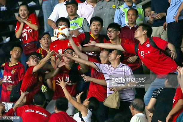 Supporters catch the official matchball during the international friendly match between FC Guangzhou Evergrande Taobao FC and FC Bayern Muenchen of...