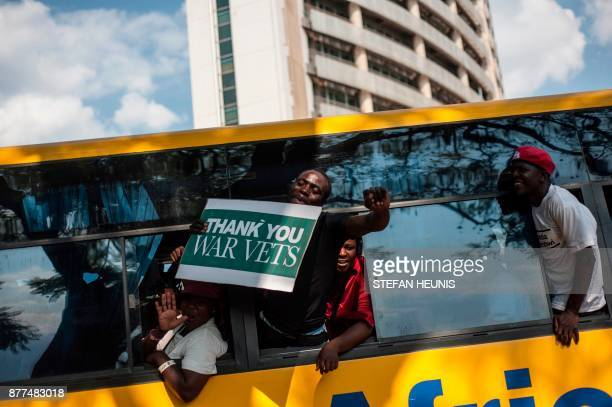 TOPSHOT Supporters celebrate from a bus upon the arrival of Zimbabwe's ousted vice president Emmerson Mnangagwa at the headquarters of Zimbabwe's...