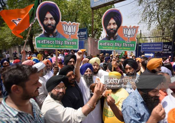 BJP supporters celebrate the victory of party candidate Majinder Singh Sirsa in Rajouri Garden bypoll on April 13 2017 in New Delhi India BJP...