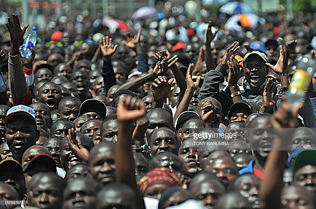 Supporters chant as they raise their arms after Kenya's Prime Minister, Vice President and Trade Minister among others announced a powerful alliance on December 4, 2012 as running mates in upcoming Kenyan presidential elections due in March. Kenya's Prime Minister Raila Odinga and Vice President Kalonzo Musyoka along with Wetangula and leaders of ten other smaller parties, signed an agreement in front of thousands of supporters to form the Coalition for Reform and Democracy (CORD) party which rivals another coalition between deputy Prime minister, Uhuru Kenyatta with opposition politician, William Ruto both of whom face indictments at the Hague based International Criminal Court (ICC). Odinga is widely tipped to be the presidential candidate with Musyoka as his deputy, although no formal announcement was made. AFP PHOTO / Tony KARUMBA