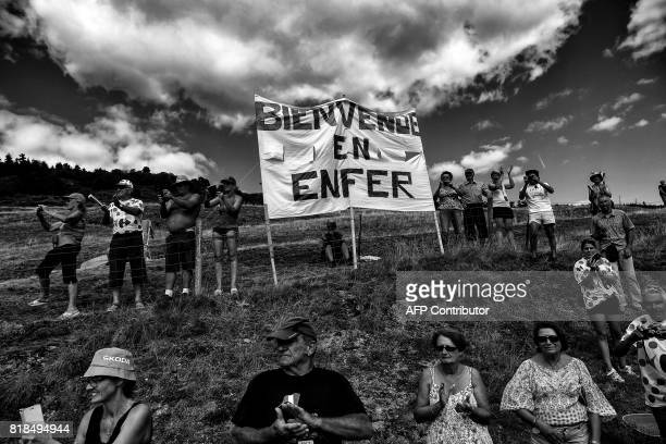 Supporters cheer along the road near a placard reading 'Welcome to Hell' during the 1895 km fifteenth stage of the 104th edition of the Tour de...