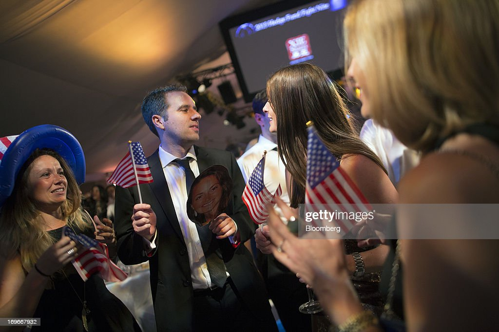 Supporters cheer and wave U.S. flags during the Hedge Fund Fight Nite 2013 charity fighting event in Hong Kong, China, on Thursday, May 30, 2013. The event raises money for Operation Breakthrough and Operation Smile charities. Photographer: Jerome Favre/Bloomberg via Getty Images