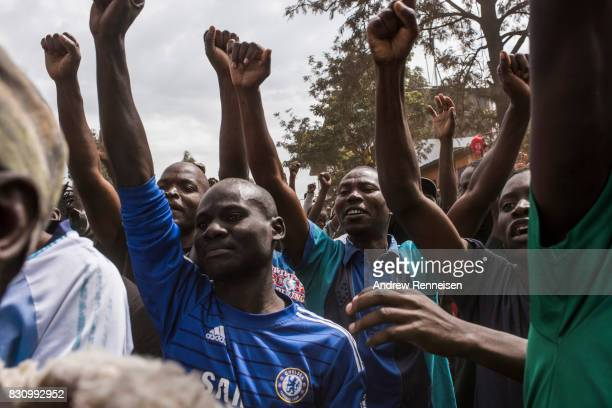 Supporters cheer as Opposition candidate Raila Odinga addresses a crowd in the Kibera slum on August 13 2017 in Nairobi Kenya A day prior...