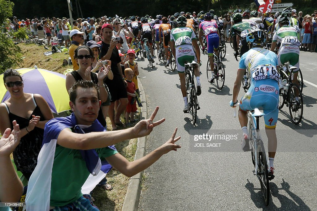 Supporters cheer cyclists along the road as the pack rides past during the 242.5 km fifteenth stage of the 100th edition of the Tour de France cycling race on July 14, 2013 between Givors and Mont Ventoux, southeastern France. AFP PHOTO / JOEL SAGET