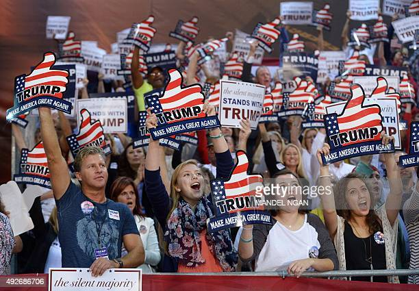 Supporters cheer during a rally for Republican presidential candidate Donald Trump at the Expo Hall of the Richmond International Raceway on October...