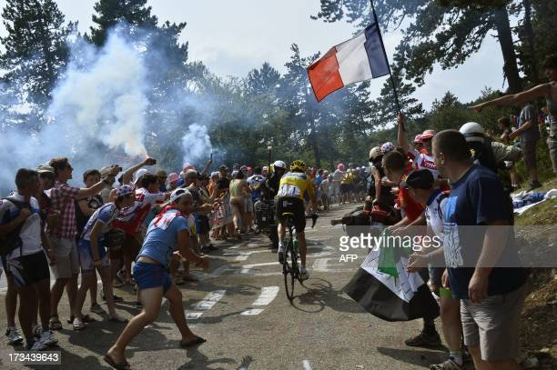Supporters cheer overall leader's yellow jersey Britain's Christopher Froome along the road during the 2425 km fifteenth stage of the 100th edition...