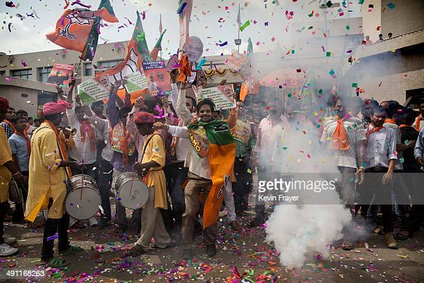 BJP supporters dance as they set off crackers as poll results come in at the party's headquarters on May 16 2014 in Ahmedabad India Early indications...