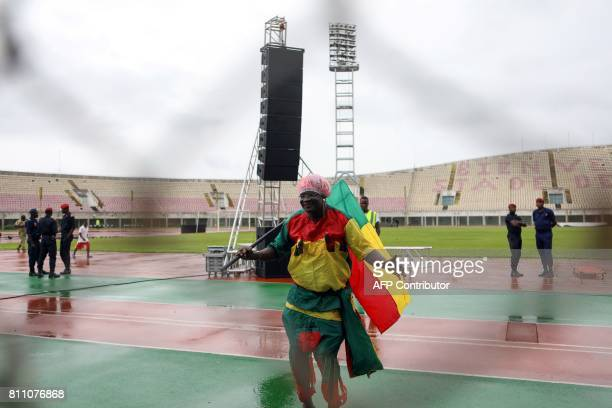 A supporters dances in the rain ahead of the match between Union Sportive Seme Krake and the Roquins de l'Atlantique at the Mathieu Kerekou stadium...