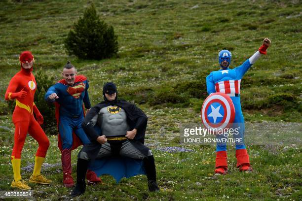 Supporters disguised as super heros pose along the road during the 177 km fourteenth stage of the 101st edition of the Tour de France cycling race on...