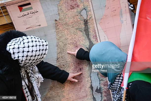 Supporters during a rally against Israel's military incursions in Gaza pointing at the map on the table Palestine supporters and sympathizers...
