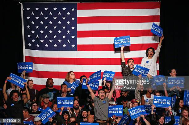 Supporters for Democratic Presidential candidate Bernie Sanders stand up and cheer as he takes the stage to speaks at a rally on February 13 2016 in...