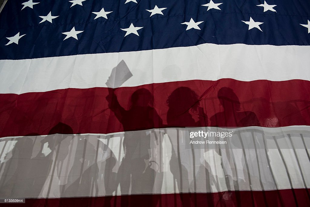 Supporters for Democratic presidential candidate Hillary Clinton are silhouetted in a large American flag at a rally following Super Tuesday on March...