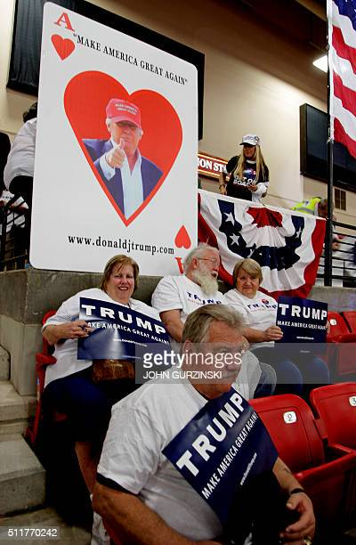 Supporters for Republican presidential candidate Donald Trump sit under an ace of hearts sign as they await Trump's appearance at the South Point...