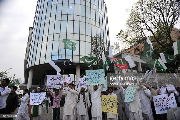 Supporters from the Pakistani religious group Sunni United Council carry placards as they gather in front of the Geo television building during an...