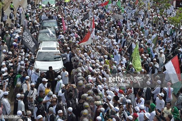 TOPSHOT Supporters gather around a vehicle transporting Rizieq Shihab leader of the Indonesian hardline Muslim group FPI as he heads to the police...