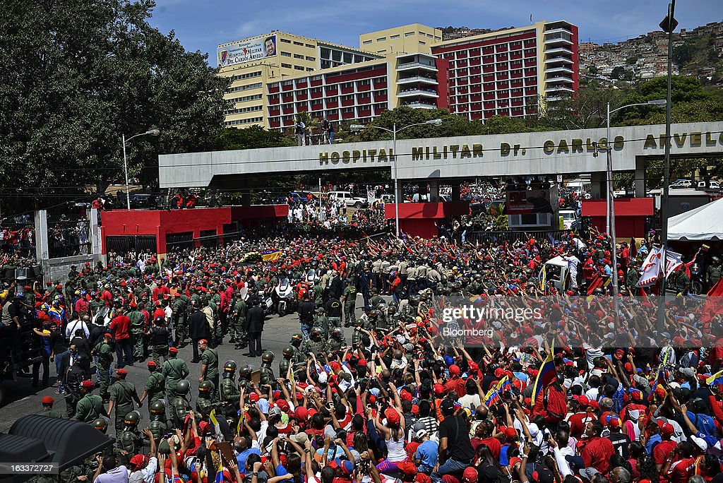 Supporters gather around the casket as it is paraded from the Carlos Arvelo military hospital during the funeral for Venezuelan President Hugo Chavez in Caracas, Venezuela, on Friday, March 8, 2013. Allies of Venezuela's Hugo Chavez paid their final respects to the firebrand socialist leader at a state funeral that marked the emotional high point of a week of tributes preceding a snap election to choose his successor. Photographer: Meridith Kohut/Bloomberg via Getty Images