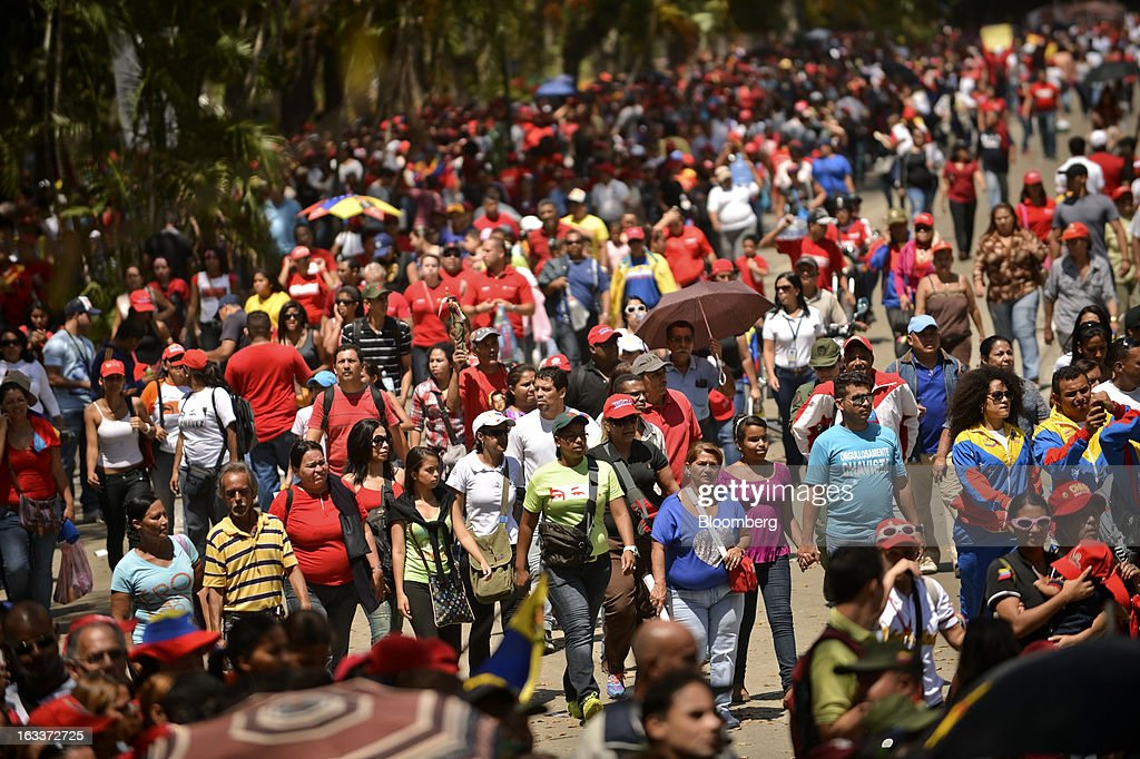 Supporters gather to pay their respects during the funeral for Venezuelan President Hugo Chavez in Caracas, Venezuela, on Friday, March 8, 2013. Allies of Venezuela's Hugo Chavez paid their final respects to the firebrand socialist leader at a state funeral that marked the emotional high point of a week of tributes preceding a snap election to choose his successor. Photographer: Meridith Kohut/Bloomberg via Getty Images