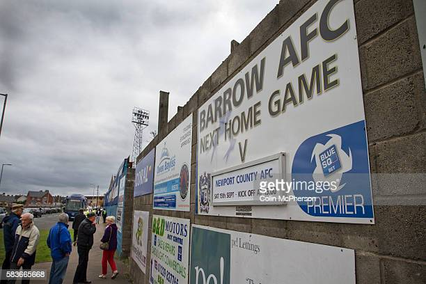 Supporters gathering on Holker Street next to sign advertising the match at Barrow AFC's Furness Building Society Stadium prior to the delayed...