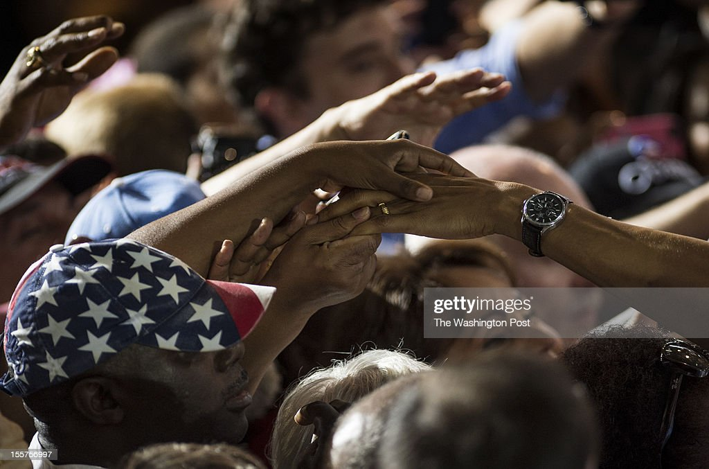 Supporters grasp President Barack Obama's hand as he works the rope line during a campaign stop at Kissimmee Civic Center in Kissimmee Florida on...