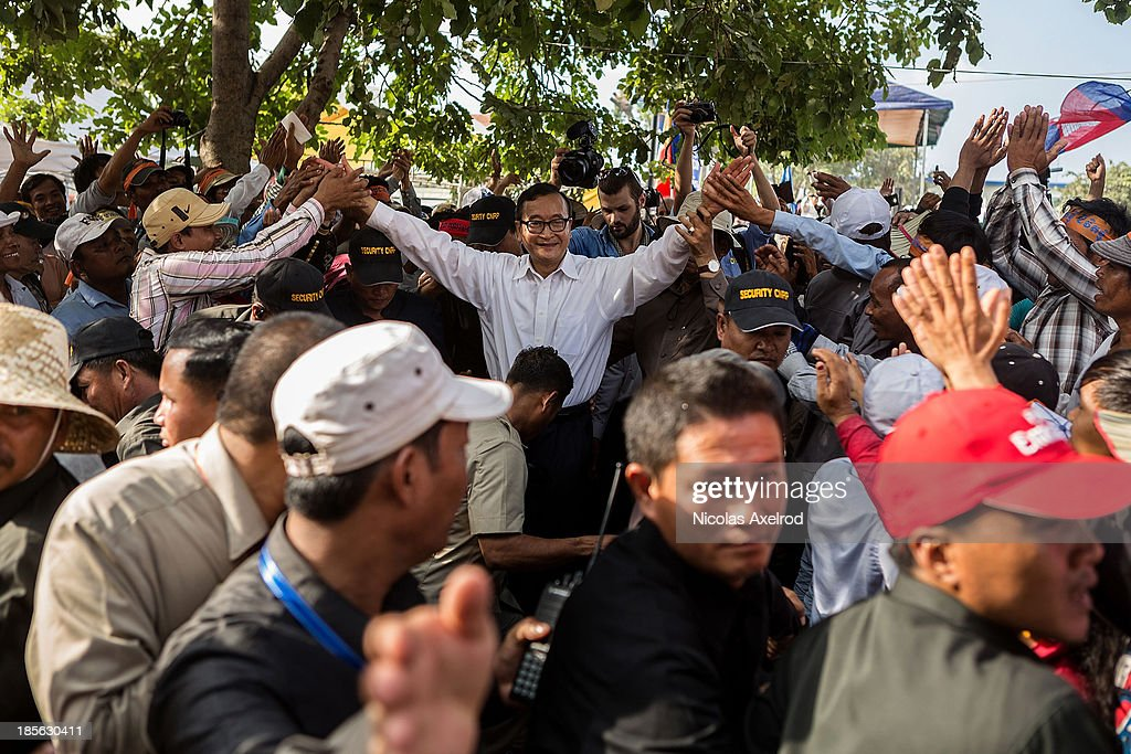 Supporters greet <a gi-track='captionPersonalityLinkClicked' href=/galleries/search?phrase=Sam+Rainsy&family=editorial&specificpeople=660347 ng-click='$event.stopPropagation()'>Sam Rainsy</a>, President of the CNRP as he starts a march to the UN offices to deliver a petition on October 23, 2013 in Phnom Penh, Cambodia. The Cambodian National Rescue Party hold the first day of a three day protest in commemoration of the 22nd anniversary of the October 23, 1991 Paris Peace Accords. The CNRP delivered a petition of over 2 million thumbprints to the UN Cambodia Office of the High Commissioner for Human Rights asking for the UN to assist in resolving the current political deadlock caused by a dispute over the country's July elections.