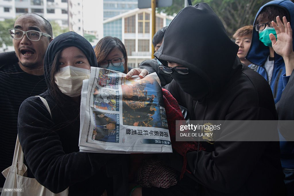 Supporters help a protester (covered by newspaper), who is facing one count of taking part in the February 9 riot in the district of Mongkok, to a taxi after a court hearing in Hong Kong on February 11, 2016. More than 30 people were expected to appear in court charged with rioting after clashes erupted in the city over official attempts to remove illegal street hawkers during the Lunar New Year. AFP PHOTO / DALE DE LA REY / AFP / DALE de la REY