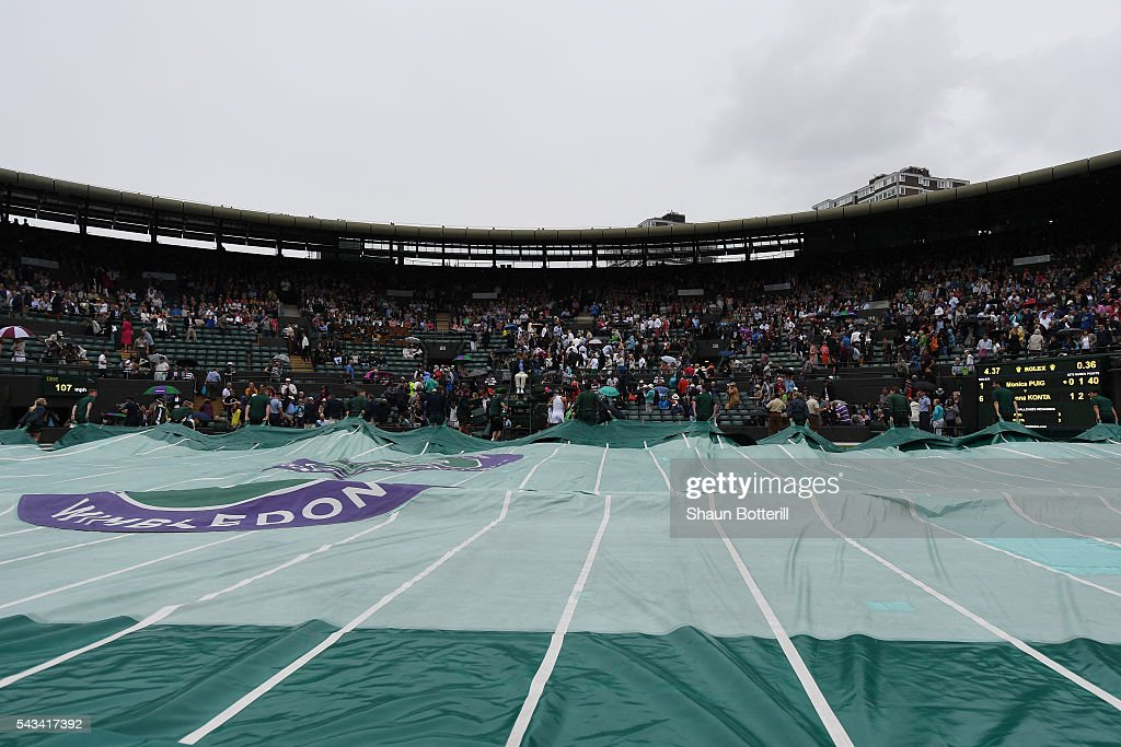 Supporters hide underneith their umbrellas as the covers come across on court one during day two of the Wimbledon Lawn Tennis Championships at the All England Lawn Tennis and Croquet Club on June 28, 2016 in London, England.