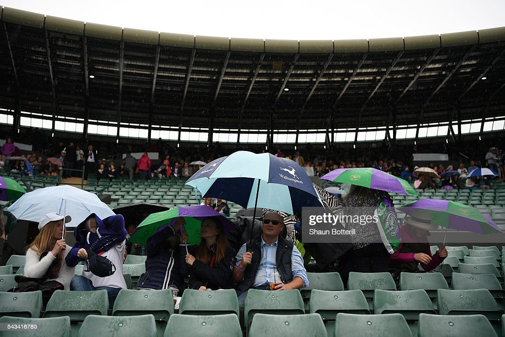 Supporters hide underneith their umbrellas on court one during day two of the Wimbledon Lawn Tennis Championships at the All England Lawn Tennis and Croquet Club on June 28, 2016 in London, England.