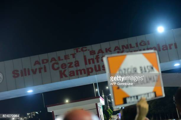 Supporters hoist posters while they wait for the release of seven people from Silivri prison in Istanbul on July 28 2017 following a Turkish court...