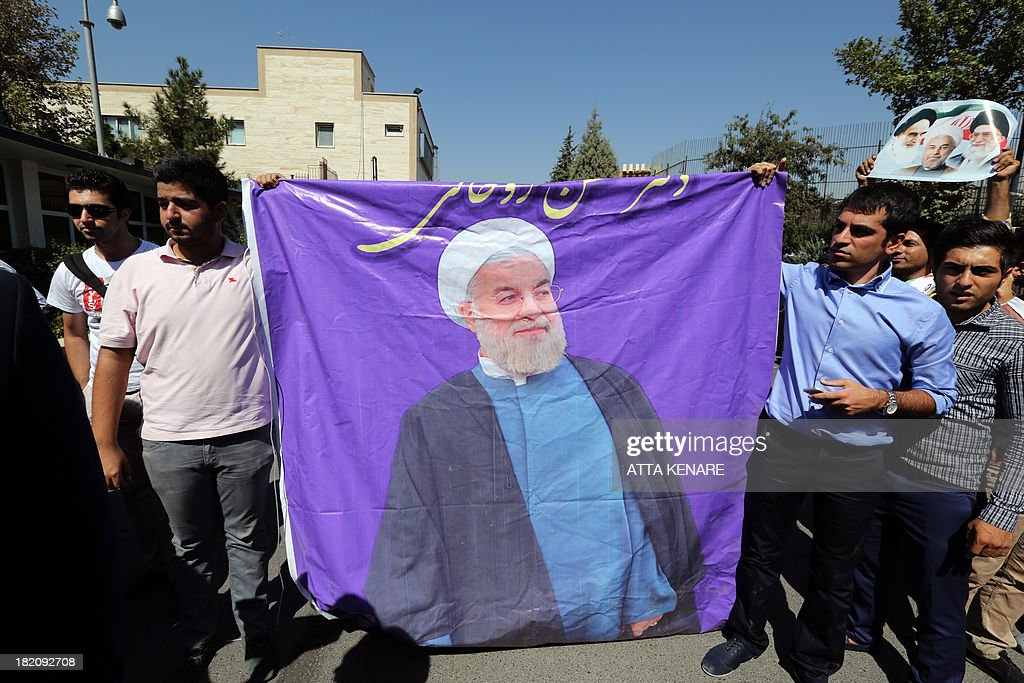 Supporters hold a banner depicting Iranian president Hassan Rouhani as his motorcade leaves Tehran's Mehrabad Airport upon his arrival from New York, on September 28, 2013. Some 60 hardline Islamists chanted 'Death to America' and 'Death to Israel' but they were outnumbered by 200 to 300 supporters of the president who shouted: 'Thank you Rouhani.'
