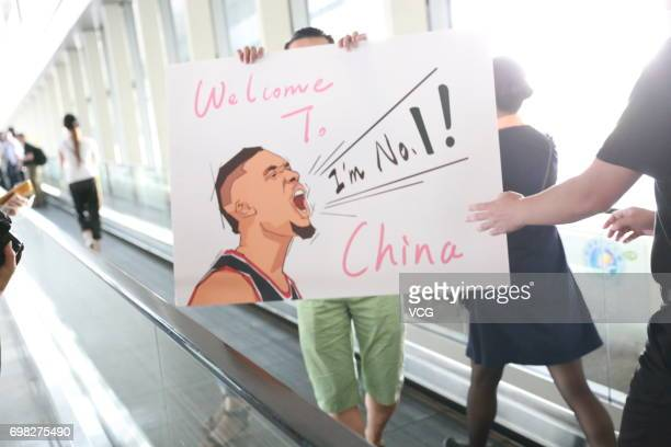 Supporters hold a poster as NBA player Damian Lillard of the Portland Trail Blazers arrives at Beijing Capital International Airport on June 20 2017...