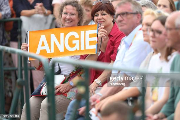 Supporters hold a sign as Angela Merkel Germany's chancellor and Christian Democratic Union leader not pictured speaks during an election campaign...