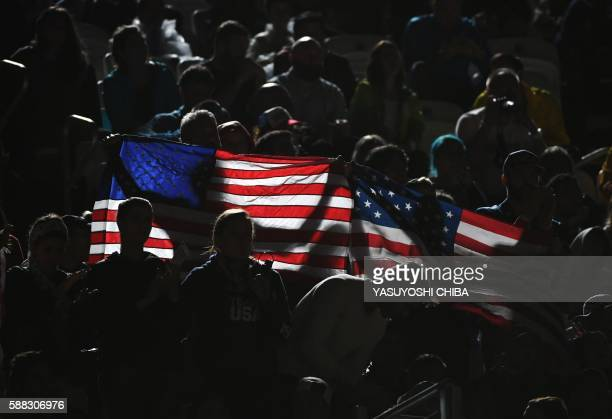 Supporters hold a US flag during the women's beach volleyball qualifying match between the USA and Switzerland at the Beach Volley Arena in Rio de...
