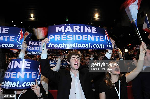 Supporters hold banners after the speech of newly elected president of French farright party Front national Marine Le Pen at the end of the party's...