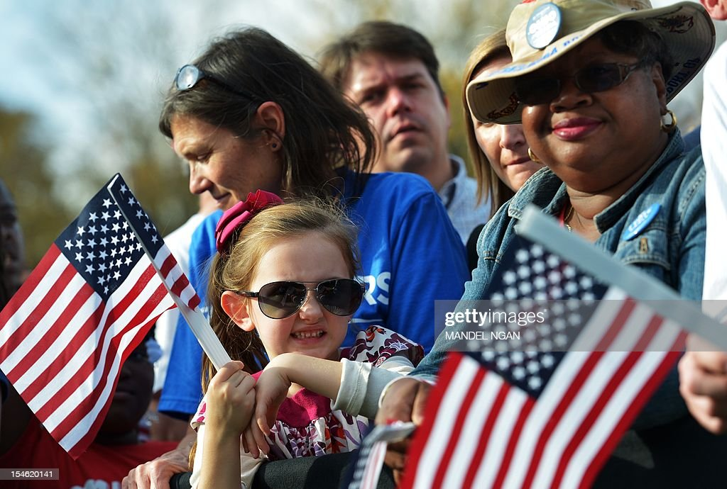 Supporters hold flags as they wait for the arrival of US President Barack Obama at a campaign rally October 23 2012 at Triangle Park in Dayton Ohio...