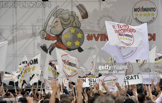M5S supporters hold flags of their party as theywait antiestablishment 5Star Movement party leader Beppe Grillo on May 23 2014 in Rome's Piazza San...