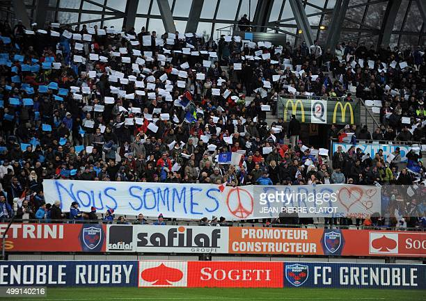 Supporters hold French flags and a banner picturing the #prayforParis sign and an inscription which translates as 'We are Paris' in tribute to the...